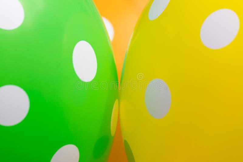 Hintergrund des Grüns orange und gelbe Ballone mit den weißen Kreisen auf ihnen Das optimistische Bild, das Symbol des Glückes lizenzfreie stockfotografie