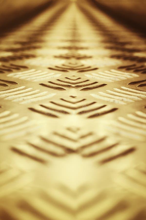 Hintergrund des Metalls mit einem wiederholenden Muster der Bronzefarbe Nahaufnahme, selektiver Fokus lizenzfreies stockbild