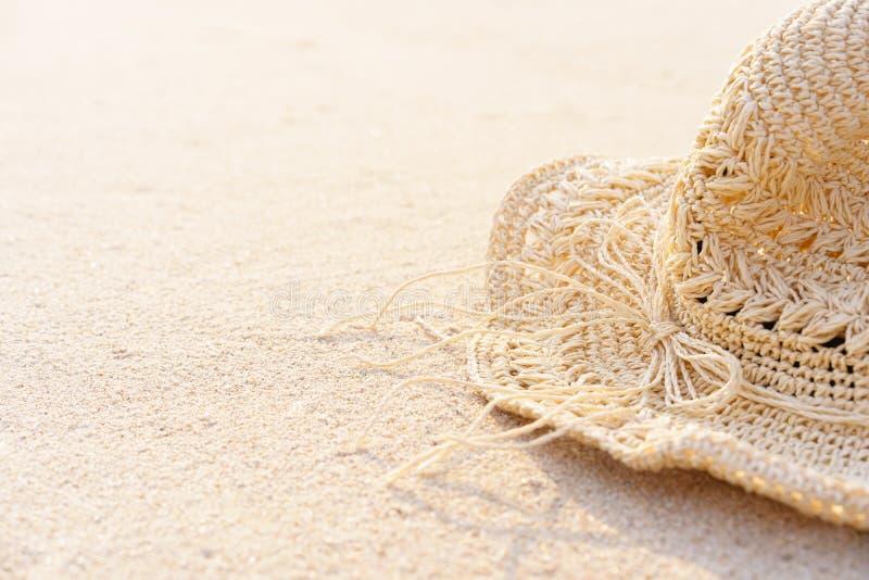 Hintergrund des Sandstrandes mit Zusatzstrohhut in der Sommerzeit Kann Text nach links hinzufügen stockbilder