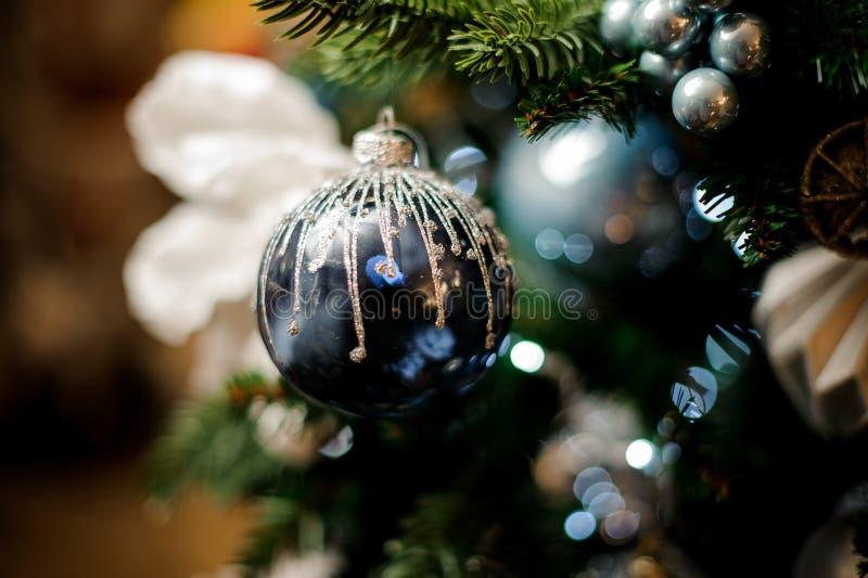 Hintergrund des Tannenbaums mit blauer Spielzeugbirne und viel Weihnachtsdekoration lizenzfreie stockbilder