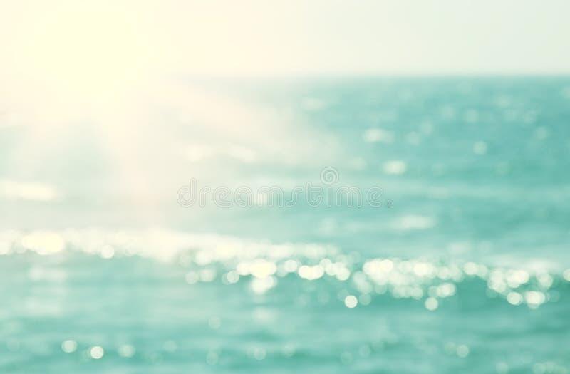 Hintergrund des unscharfen Strandes und Meereswellen mit bokeh Sonnenuntergang beleuchten lizenzfreies stockbild