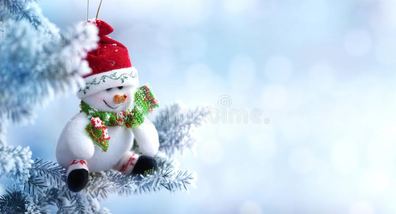 Hintergrund des Weihnachtsschneemannes hängend an einem Schnee-Baumast lizenzfreie stockfotografie