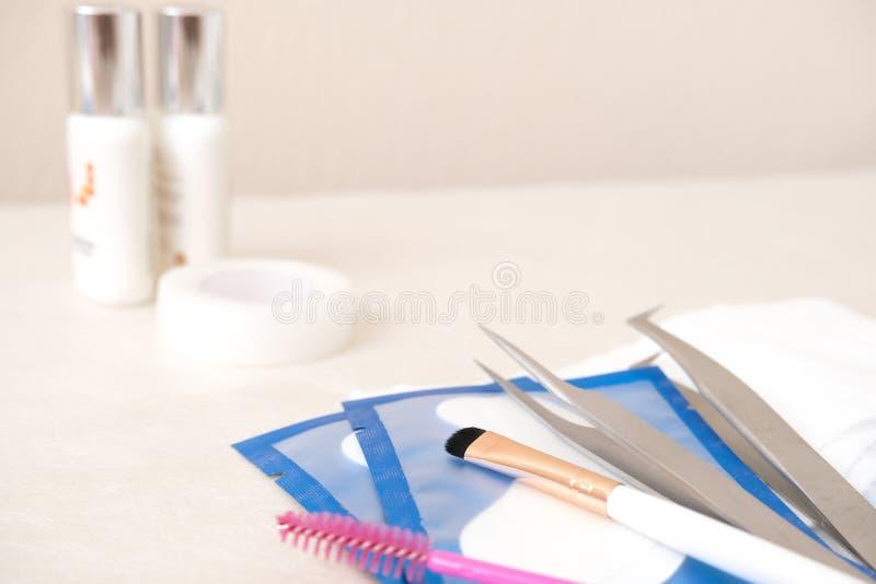 Hintergrund für Eyelash-Erweiterungsverfahren Werkzeuge Klebstoff, Pinzette, Bürsten Textkopie - Schönheitssalon, Mode und lizenzfreies stockbild