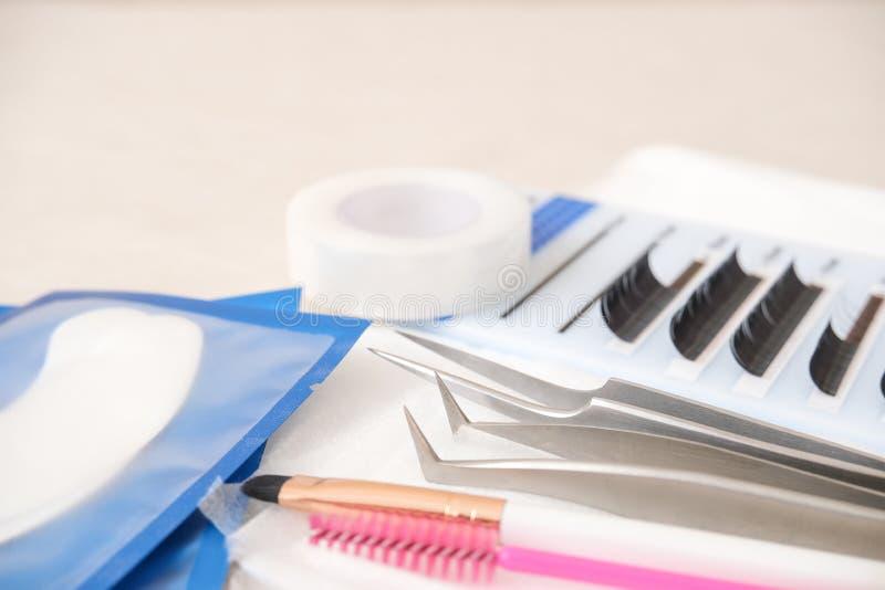 Hintergrund für Eyelash-Erweiterungsverfahren Werkzeuge Klebstoff, Pinzette, Bürsten Textkopie - Schönheitssalon, Mode und lizenzfreie stockbilder