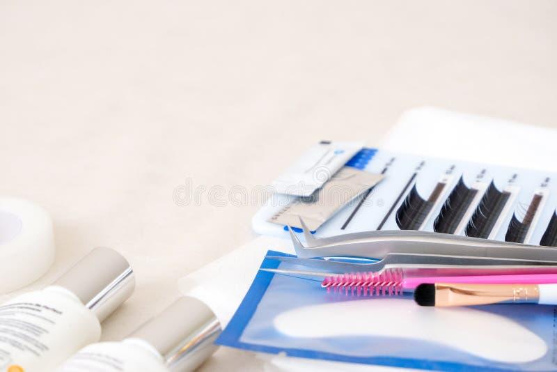 Hintergrund für Eyelash-Erweiterungsverfahren Werkzeuge Klebstoff, Pinzette, Bürsten Textkopie - Schönheitssalon, Mode und stockfotografie