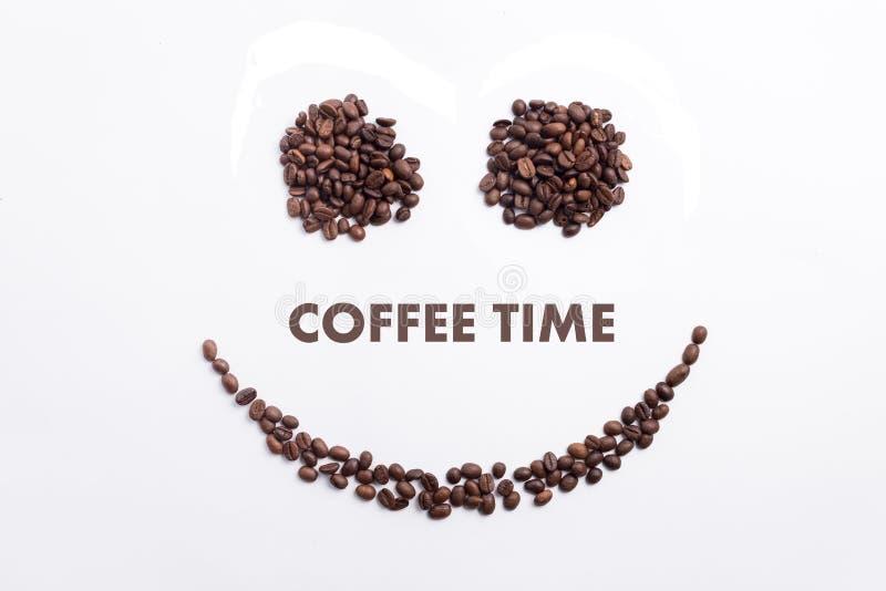 Hintergrund gemacht von den Kaffeebohnen in einer smileygesichtsform mit Mitteilung ` Kaffee-Zeit ` stockbild