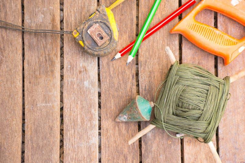 Hintergrund-Handwerkerwerkzeug haben Säge und Lot und Maßband Auf hölzernem Hintergrund Schirm für Tischler lizenzfreie stockfotos