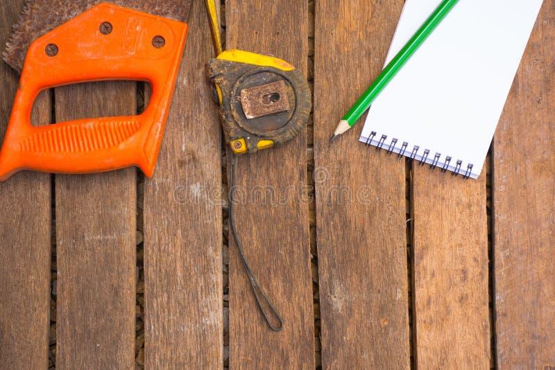 Hintergrund-Handwerkerwerkzeug haben Säge und Maßband und Holzbleistift und -notizbuch Auf hölzernem Hintergrund Schirm für Tisch stockfoto