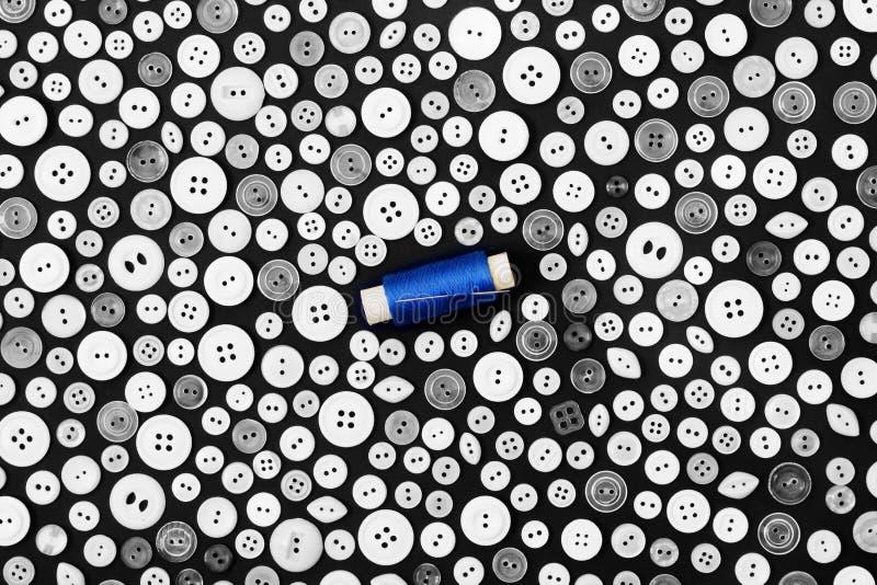 Hintergrund - helle Knöpfe auf einer dunklen Oberfläche und einer Spule des blauen Fadens mit Nadel stockbilder