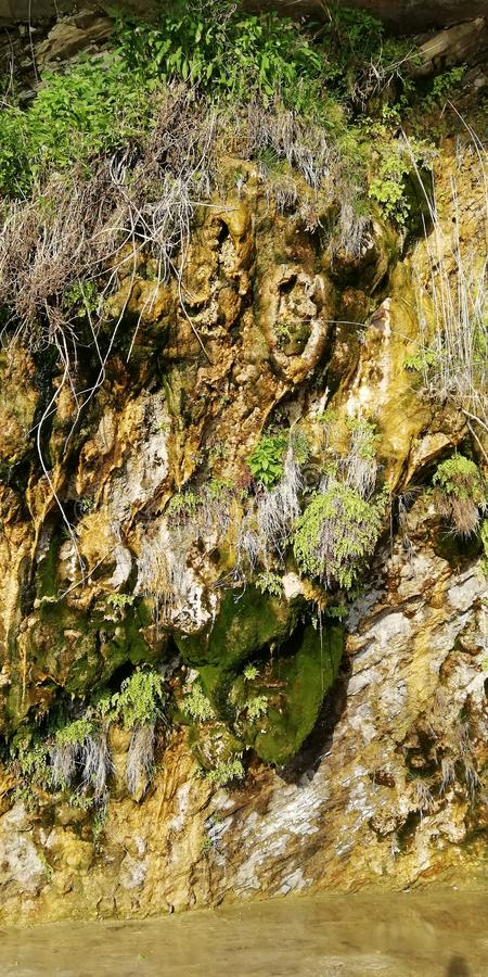 Hintergrund Launenhafte Klippen bedeckt mit Moos und Anlagen Ein seltenes natürliches Phänomen - weinende Felsen lizenzfreie stockfotografie