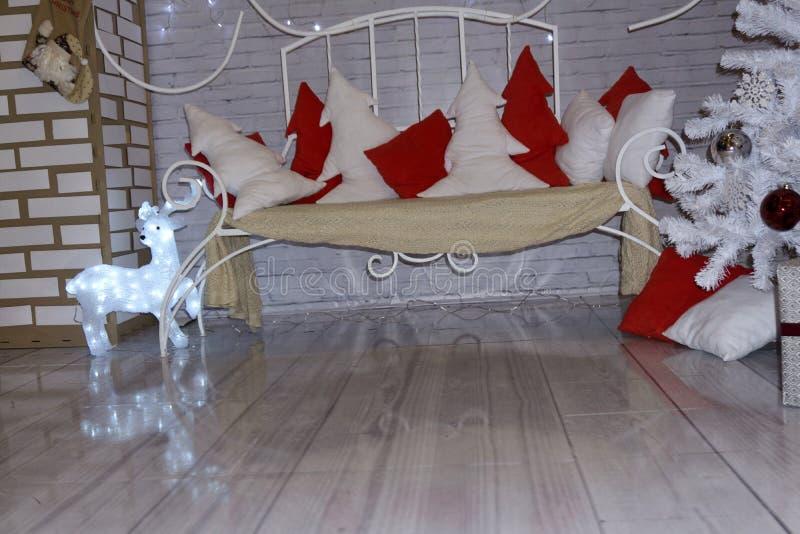 Hintergrund Luxuswohnzimmerinnenraum mit Sofa verzierte schicken Weihnachtsbaum, Geschenke, Plaid und Kissen stockfotografie