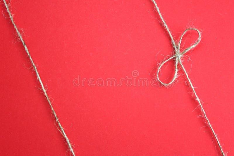 Hintergrund mit dem Bogenknoten des Seils r Jutefaserseil mit Bogen Schnur stockfotografie
