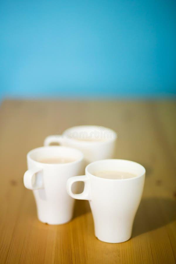Hintergrund mit drei weißen Kaffeetassen, Milchgetränk, Draufsicht lizenzfreie stockbilder