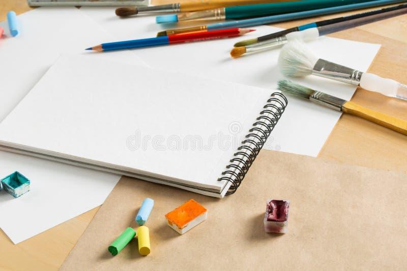 Hintergrund mit einem Satz Aquarellfarben, -bleistiften, -bürsten und -blättern Papier auf einem Holztisch stockfotos