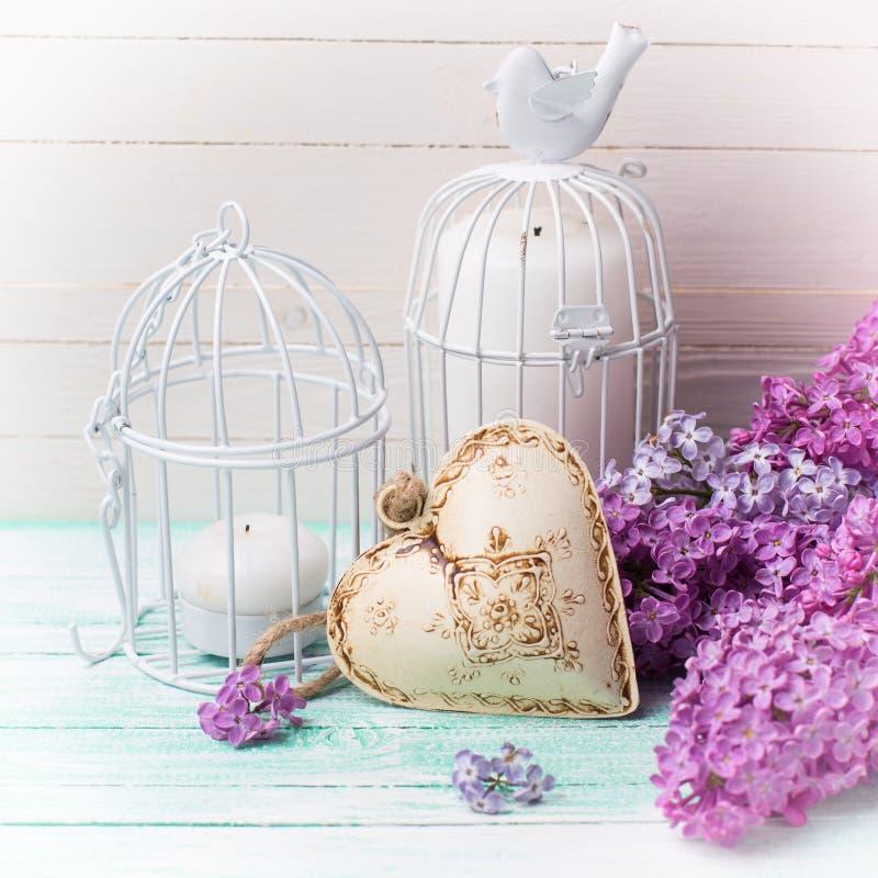 Hintergrund mit frischen lila Blumen, Kerzen im dekorativen Vogel lizenzfreie stockfotos