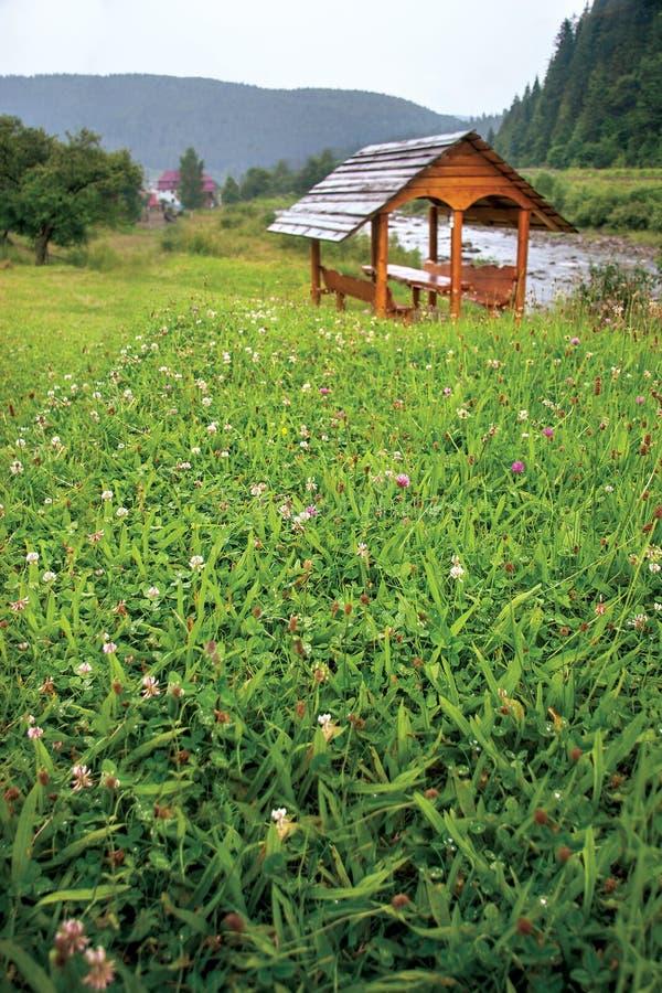 Hintergrund mit grünem Gras, Kleeblumen, einem hölzernen Gazebo mit einem Fluss, Bergen und einem Dorf im Hintergrund lizenzfreie stockfotos