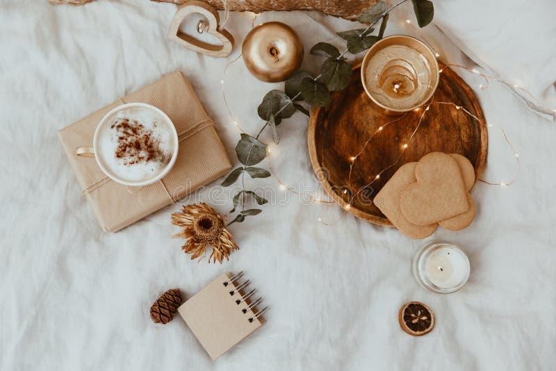 Hintergrund mit Kaffeetasse, Plätzchen und Golddekorationen im Bett lizenzfreie stockfotografie
