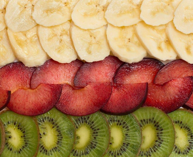 Hintergrund mit Kiwi, Pflaumen und Bananen lizenzfreie stockfotografie