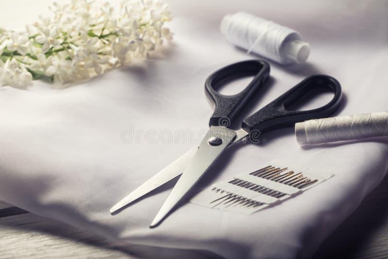 Hintergrund mit nähenden Hilfsmitteln Scheren, Spulen mit Thread und Nadeln und Gewebe auf weißer Tabelle stockfotos