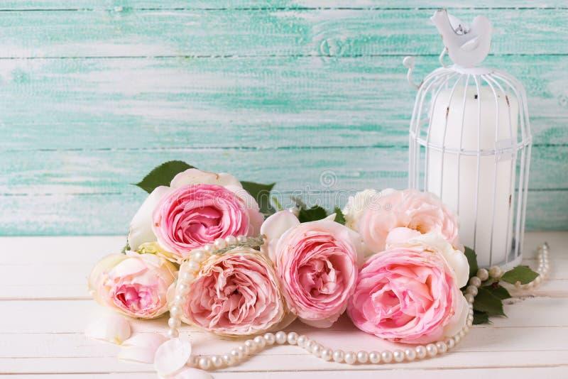 Hintergrund mit rosa Rosenblumen, -perle und -kerze im Dekorum stockbild