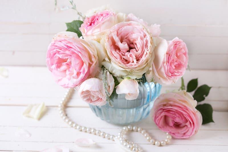 Hintergrund mit süßen rosa Rosen blüht im blauen Vase auf Weiß stockfoto