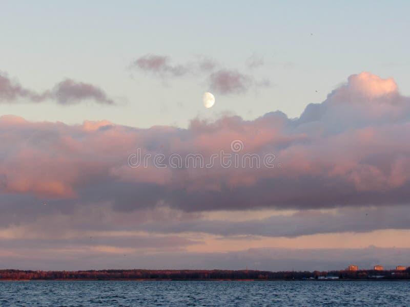 Hintergrund mit steigendem Mond über rosa Sonnenuntergangwolken stockbild