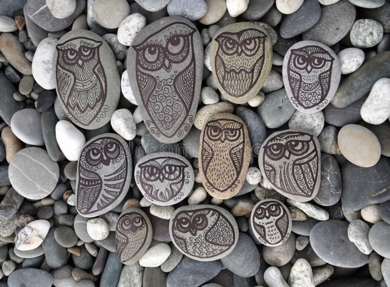Hintergrund mit Steinen mit gemalten Dekoreulen stockfotografie
