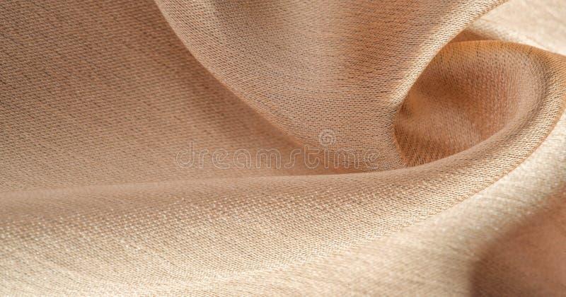 Hintergrund, Muster, Textur, beigefarbene goldene Seidengewebe Es ist glatt matt und durch ein leicht verdrehtes Garn haltbar lizenzfreie stockbilder