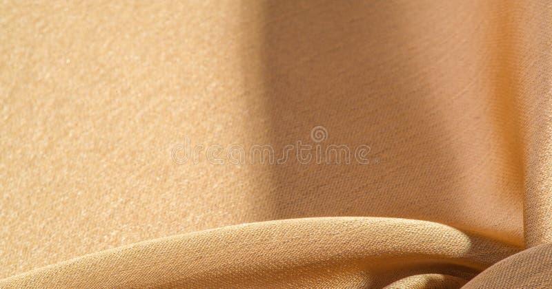 Hintergrund, Muster, Textur, beigefarbene goldene Seidengewebe Es ist glatt matt und durch ein leicht verdrehtes Garn haltbar stockfotografie
