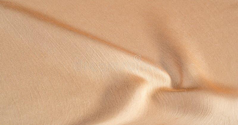 Hintergrund, Muster, Textur, beigefarbene goldene Seidengewebe Es ist glatt matt und durch ein leicht verdrehtes Garn haltbar lizenzfreie stockfotos