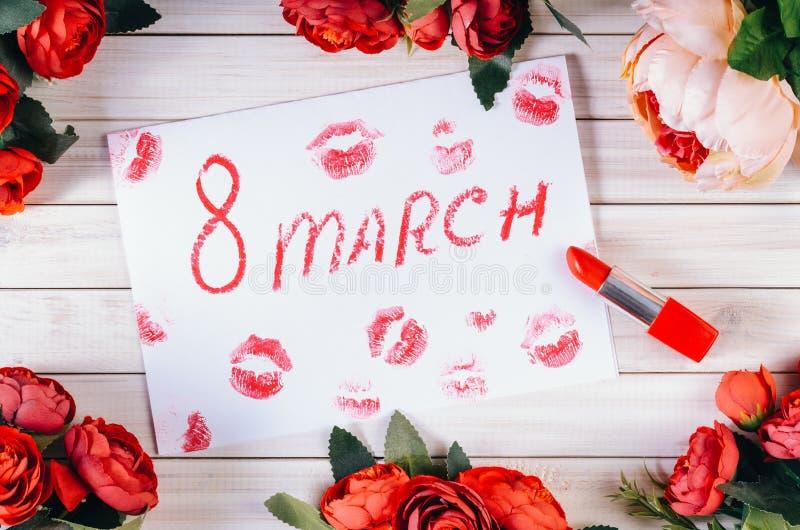 Hintergrund roter Rosen, Lippenstift und Drucke von Frauenlippen auf einem Holztisch für den Internationalen Frauentag stockfoto