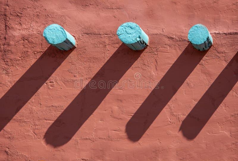 Hintergrund - Türkiskragsteine und ihre langen Schatten auf einer orange Stuckwand auf südwestlichem Artgebäude lizenzfreie stockbilder
