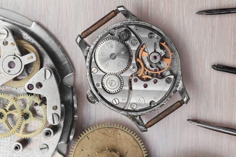 Hintergrund von alte auseinandergebaute Uhren und Reparaturwerkzeuge stockfotografie
