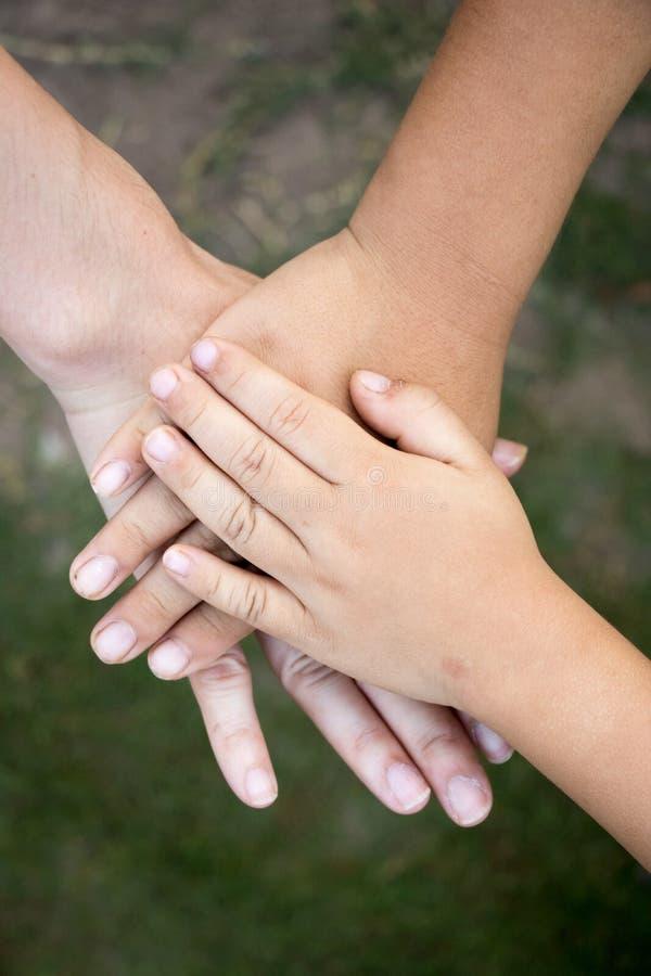 Hintergrund von Händen des asiatischen weiblichen Erwachsenen und zwei Kinder gruppieren Berufskleidung lizenzfreie stockfotos