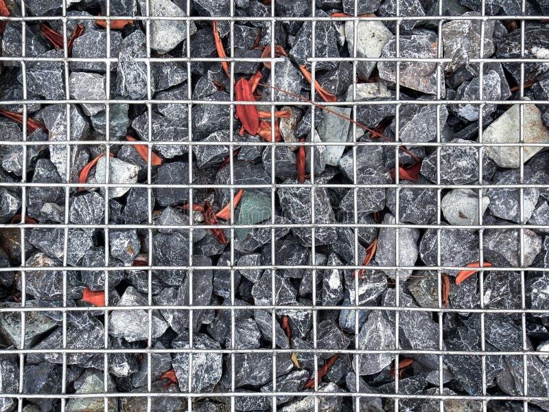 Hintergrund von Kies-Steinen mit trockenen Blättern unter Metalldraht-Masche lizenzfreie stockfotos