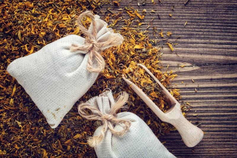 Hintergrund von medizinischen Kräutern der trockenen Ringelblume, zwei Kissentaschen gesunder Calendula stockbilder
