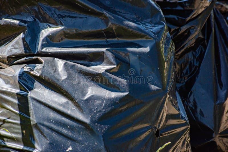 Hintergrund von schwarzen Abfalltaschen stockfotos