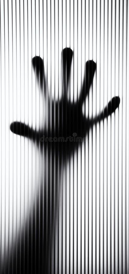 Hintergrundbeleuchtete Fingerspitzen gedrückt gegen geplätschertes Glas lizenzfreie stockfotos