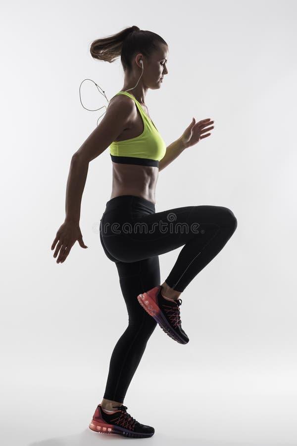 Hintergrundbeleuchtetes Schattenbild des weiblichen Läufers im gelben Trägershirt hohe Knie tuend trainieren stockfoto