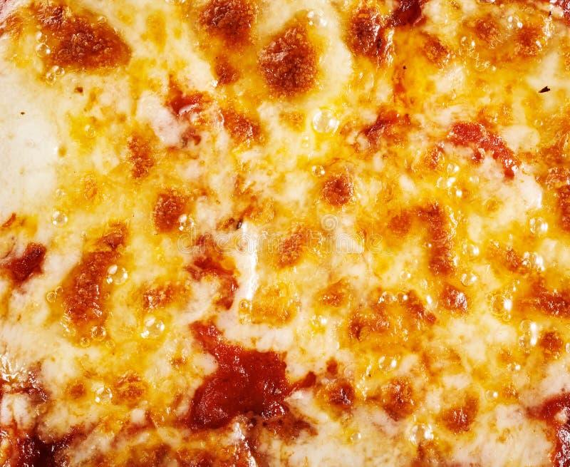 Hintergrundbeschaffenheit des geschmolzenen Mozzarellas auf einer Pizza lizenzfreie stockfotografie