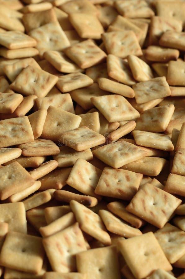 Hintergrundbeschaffenheit von den kleinen essbaren Quadraten gebacken vom Teig und mit Salz besprüht Viel Salz cracke lizenzfreies stockbild