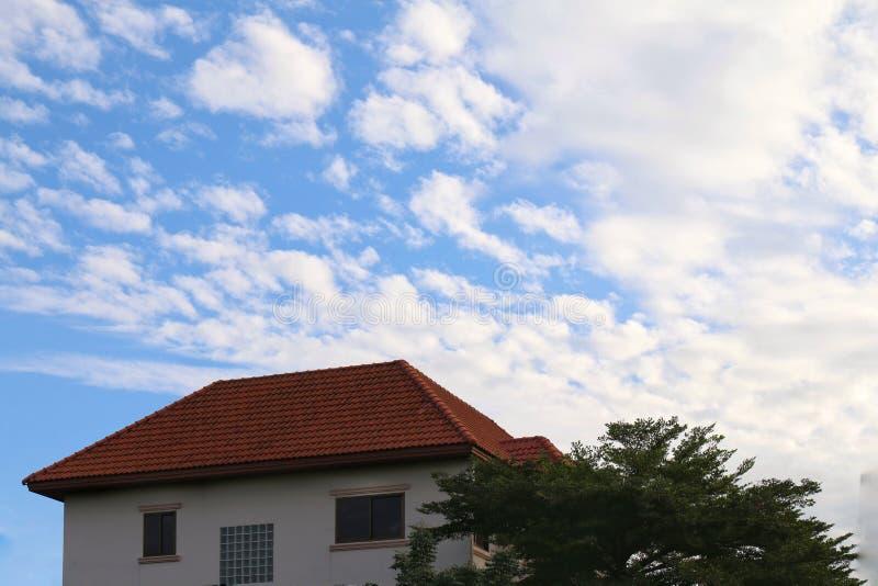 Hintergrundhimmel mit Häusern auf der Unterseite des Bildbildgroßen, Hauptdachs und des Baums, Landschaftseigentumsdorf auf blaue lizenzfreie stockbilder