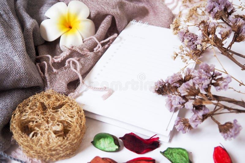 Hintergrundschablonen mit leerem Textraum auf Notizbüchern auf dem Gewebe und den dekorativen Trockenblumen stockfoto