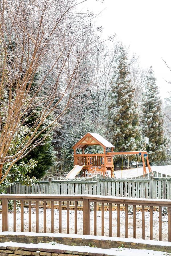 Hinterhof-Spielplatz und Zaun im Schnee lizenzfreie stockfotografie