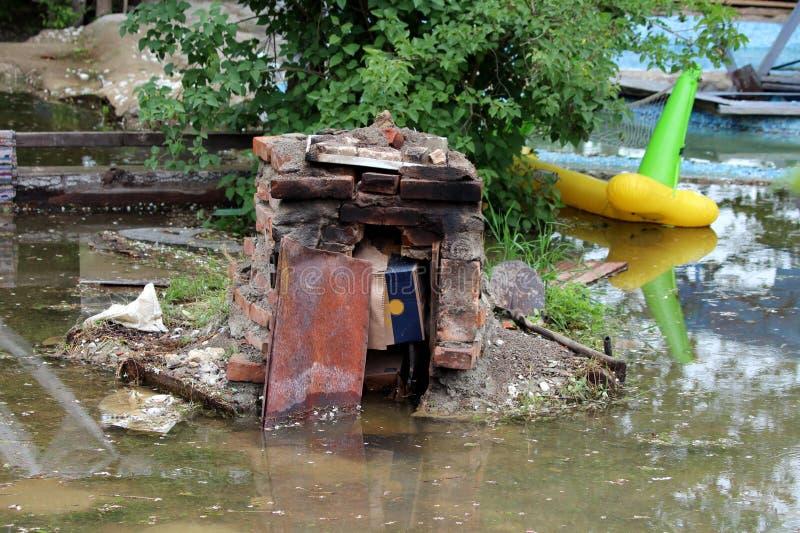 Hinterhofgrill des roten Backsteins vollständig zerstört während der Naturkatastrophe umgeben mit schlammigem Hochwasser und defe stockbilder