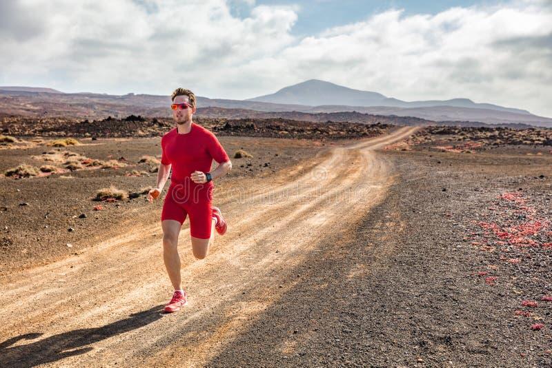 Hinterlaufender Athleteneignungs-Mannläufer, der auf tragender Kompressionskleidung des Wüstenschotterwegs und tragbarem Technolo lizenzfreie stockbilder