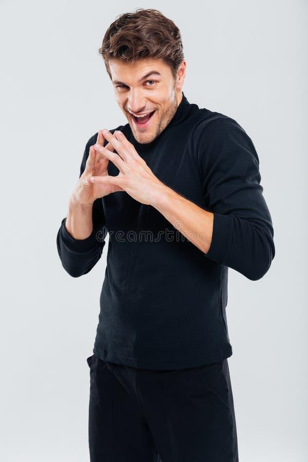 Hinterlistiger schlauer junger Mann in der schwarzen stehenden und lächelnden Kleidung lizenzfreie stockbilder