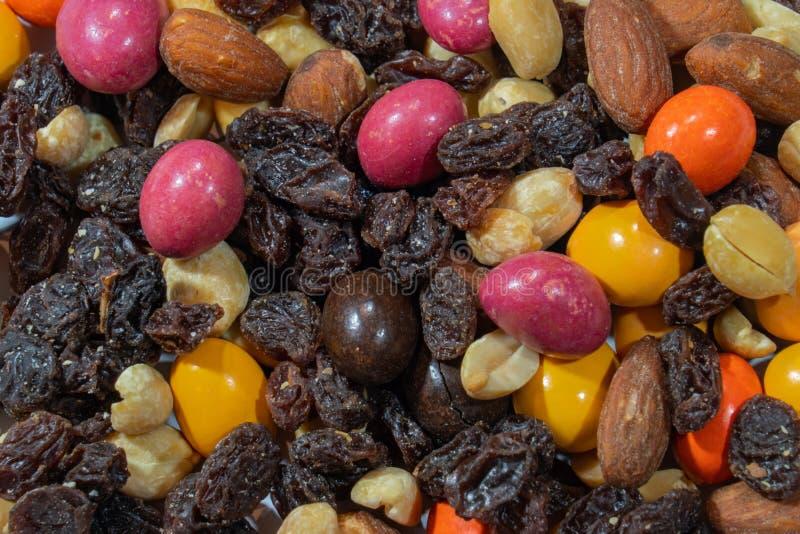 Hintermischungsabschluß herauf Makro - Rosinen, Mandeln, Nüsse, Erdnüsse und bunte Pralinen lizenzfreies stockfoto