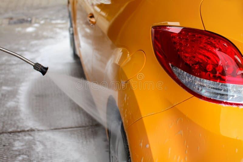 Hinterrad und Rückseite des gelben Autos, das mit Jet-Wasserst. gewaschen wird lizenzfreie stockfotografie