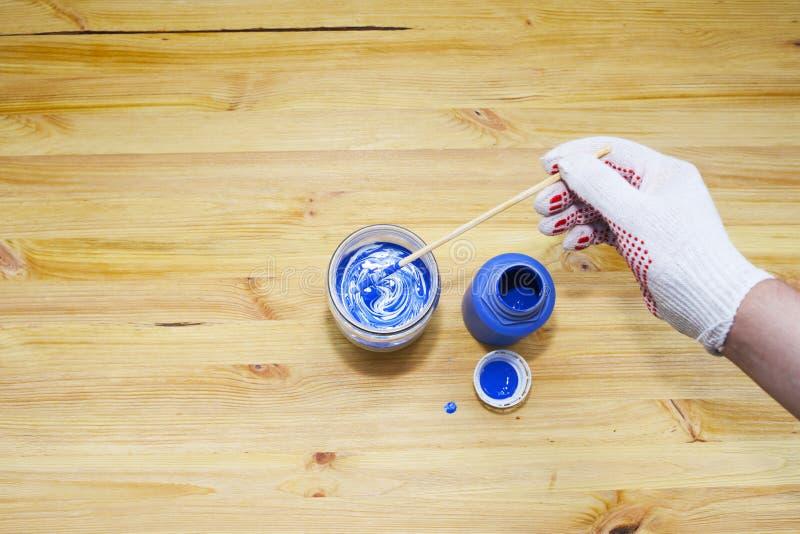 Hinzufügen der blauen Färbung einem Glas weißer Farbe Die behandschuhte Hand der Männer, hölzerner Hintergrund Maler lizenzfreies stockfoto